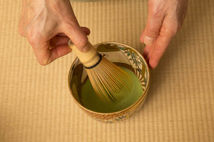 During the tea ceremony, all the gestures of both the Tea Master and guests are important. The Tea Master purifies the long spoon with a cloth of silk, warms the water to the right temperature, deposits the matcha powder in a bowl with a bamboo spoon, pours over the hot water and creates the frothy mousse of the matcha tea using a small bamboo whisk.